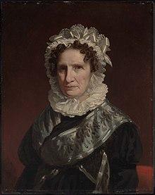 Portrait of an older woman, at half length, against a plain background. She wears a lace bonnet and ruff, and black dress with silver-gray sash and trim. Her hair is curly and auburn. She has a very pale complexion.