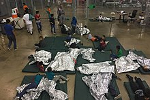 Children and juveniles in a wire mesh compartment, showing sleeping mats and thermal blankets on floor