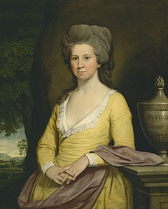 Painting of woman, at three-quarter length, wearing a yellow dress with a plunging neckline, which has a white lace trim. Her hands held together in front of her, with fingers entwined. She leans on a stone balustrade, upon which sits an inscribed stone urn. In the distance are green hills and trees.