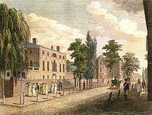 A painting of a sunlit, tree-lined street, with two prominent buildings, each behind a full-height brick wall. Passers-by include women with parasols, a man in a top hat and yellow suit, and a solder in a blue coat with red trim and a white sash.