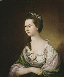 Portrait of a young woman at half length. She wears a cream top with a green shawl, and has a floral posy over her cleavage. She has flowers in her hair, which is long but swept back to expose her neck.