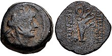 Coin of Alexander II. On the obverse, a bust of the king wearing a headdress in the shape of an elephant head. On the reverse, a ship aphlaston is shown