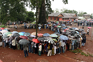 People queue in the rain to vote in parliamentary and presidential elections outside a polling station in Freetown, Sierra Leone, 11 August 2007.