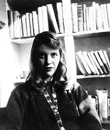 A black-and-white photo of a woman with shoulder-length hair. She is seated facing the camera, wearing a sweater, with bookshelves behind her.