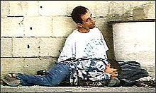 The same scene again. The man is sitting with his head hanging to his right. The boy is lying over the man's knees, with his right hand over his face. Four small holes can be seen in the wall behind them.