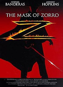 A dimly-lit figure sporting a rapier, a black costume with a flowing Spanish cape, a flat-brimmed black gaucho hat, and a black cowl sackcloth mask that covers the top of the head from eye level stands with the film's title: THE MASK OF ZORRO in white font. He is silhouetted against a red hue fading to black at the top with the star billing of ANTONIO BANDERAS and ANTHONY HOPKINS.