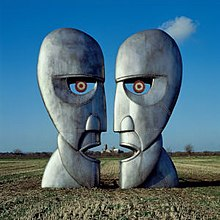 A colour photograph of two large silver-grey iron sculptures of opposing silhouetted faces. The sculptures are standing in a brown wheat field with a blue sky behind them.