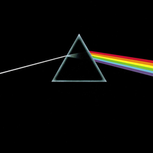 A prism refracting white light into a rainbow on a black background