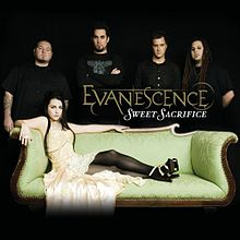 "A picture showing five people in a black room. The woman in front has black hair and a yellow dress and is lying on a couch. Four men are shown behind her and all of them are wearing black T-shirts. In front of them, the word ""Evanescence"" is written with yellow letters. Another word ""Sweet Sacrifice"" can be also seen which is written with white letters."
