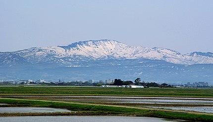 北西から望む月山と鶴岡市街。