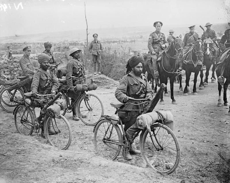 Indian soldiers with bicycles. Soldiers on horses looking on.