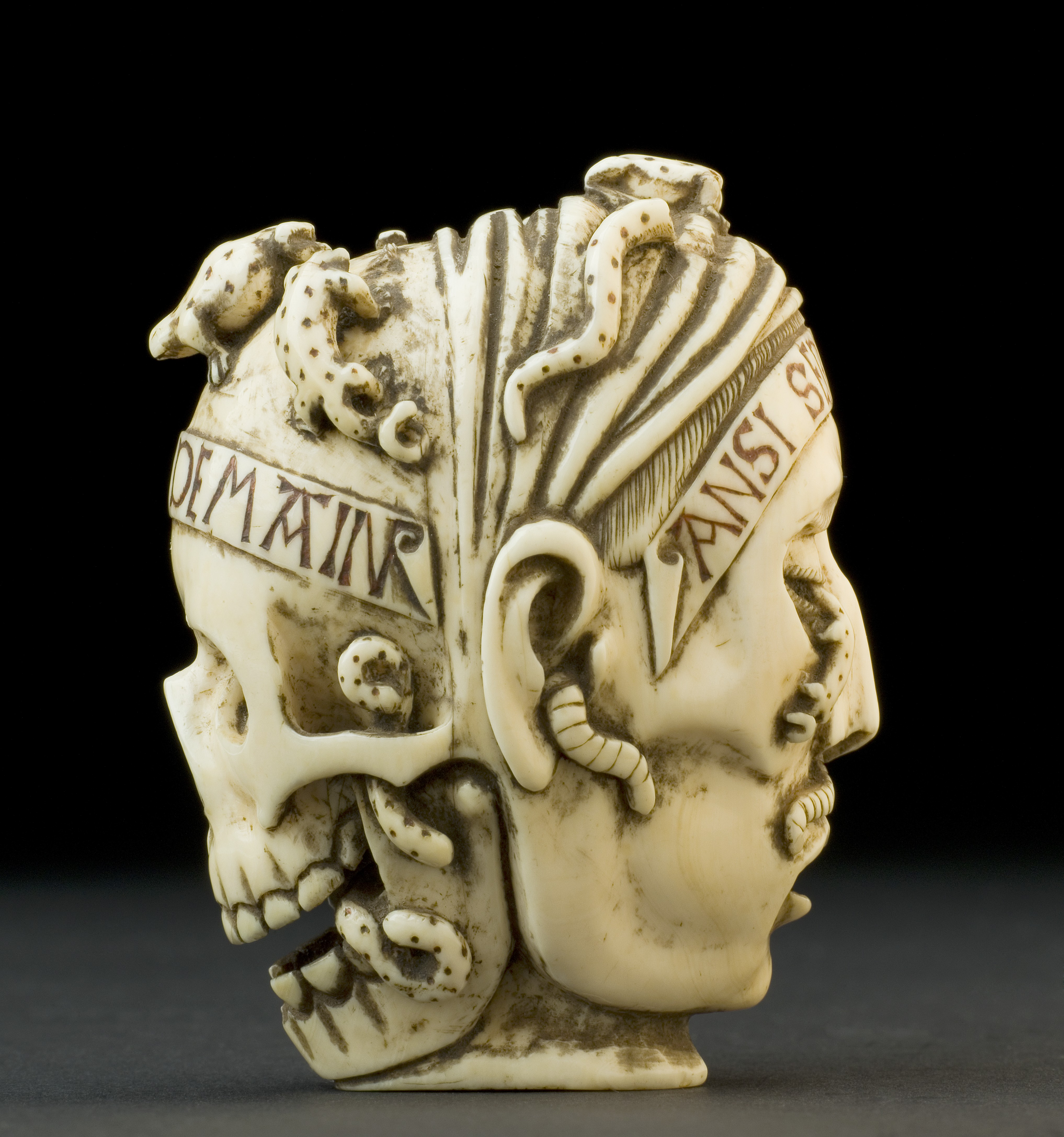 Ivory carving of the front of a skull on one side and the face of a