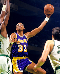 "A man, wearing a purple jersey with the word ""LAKERS"" and the number 33"