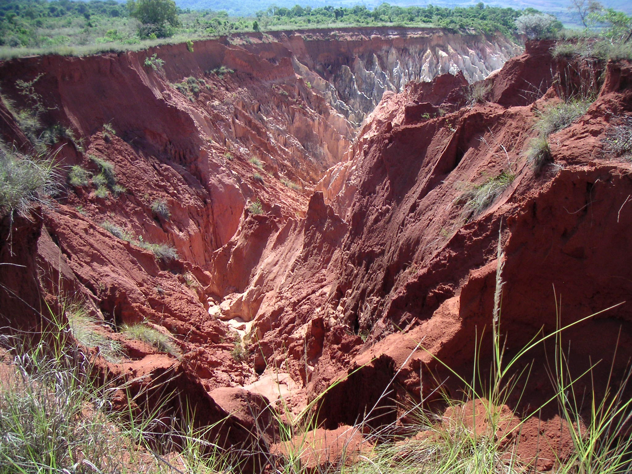 A vast, red soil gully caused by erosion
