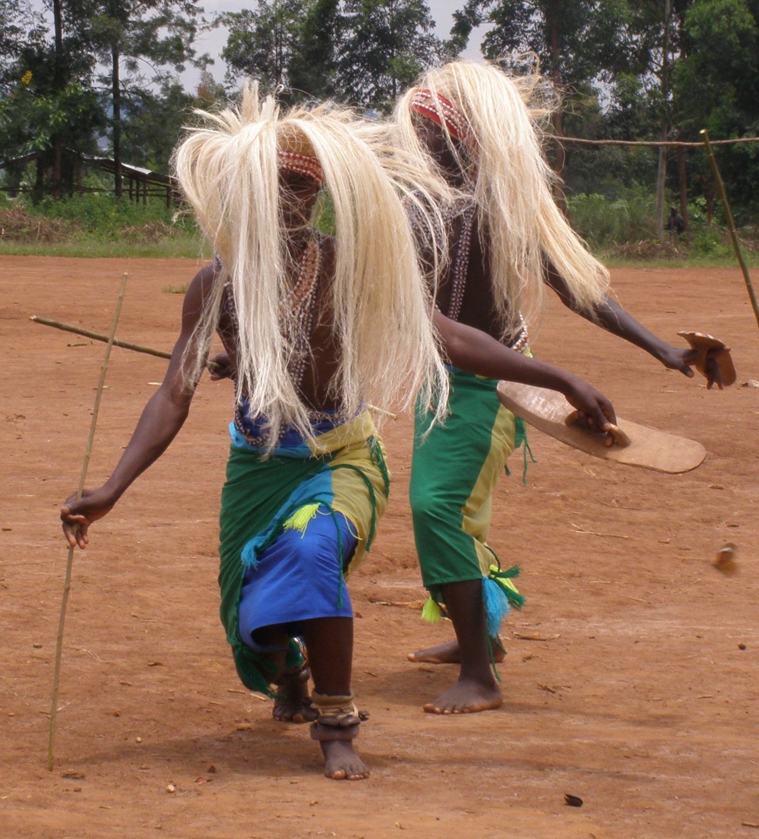 Photograph depicting two male dancers with straw wigs, neck garments, spears and sticks