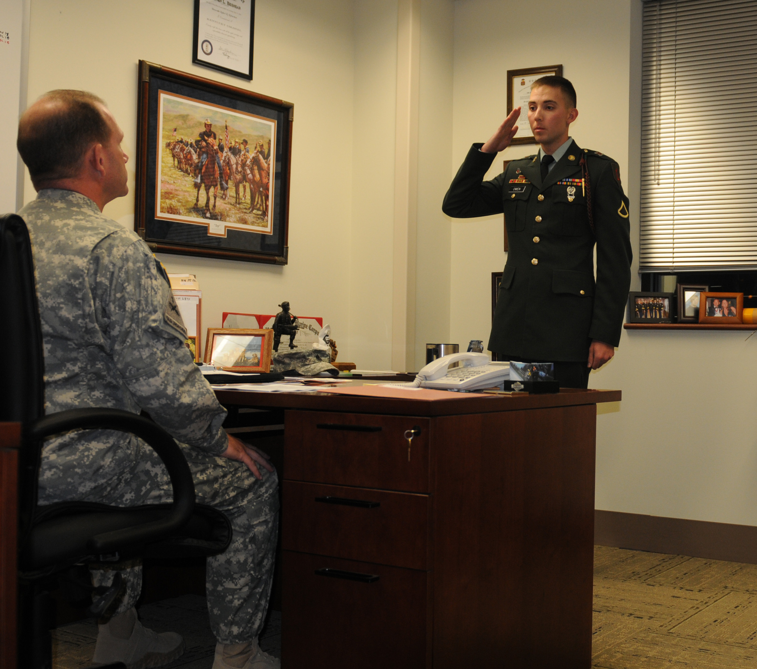Soldier saluting a superior officer seated behind a desk