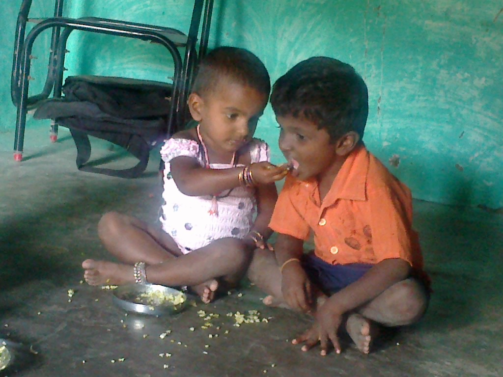 Description Tamil Child share the food to his brother.jpg