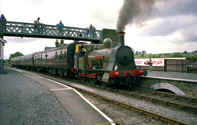 steam locomotive and carriages passing under a lattice footbridge