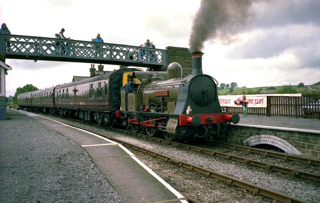 steam locomotive and carriages passing under a lattice footbridge