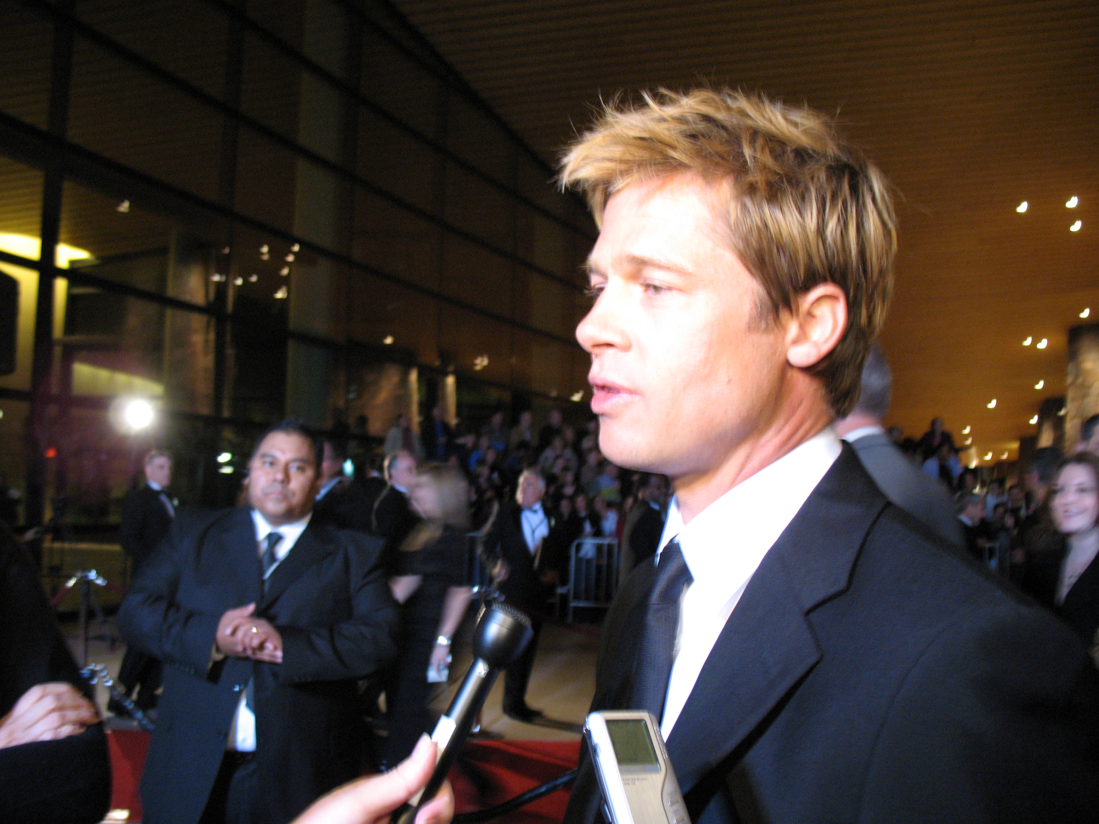A Caucasian male with dyed blonde hair is being interviewed. He is wearing a black suit and tie, with a white shirt, and is standing on a red carpet. People standing behind barricades are visible in the background, while microphones are visible in the foreground.