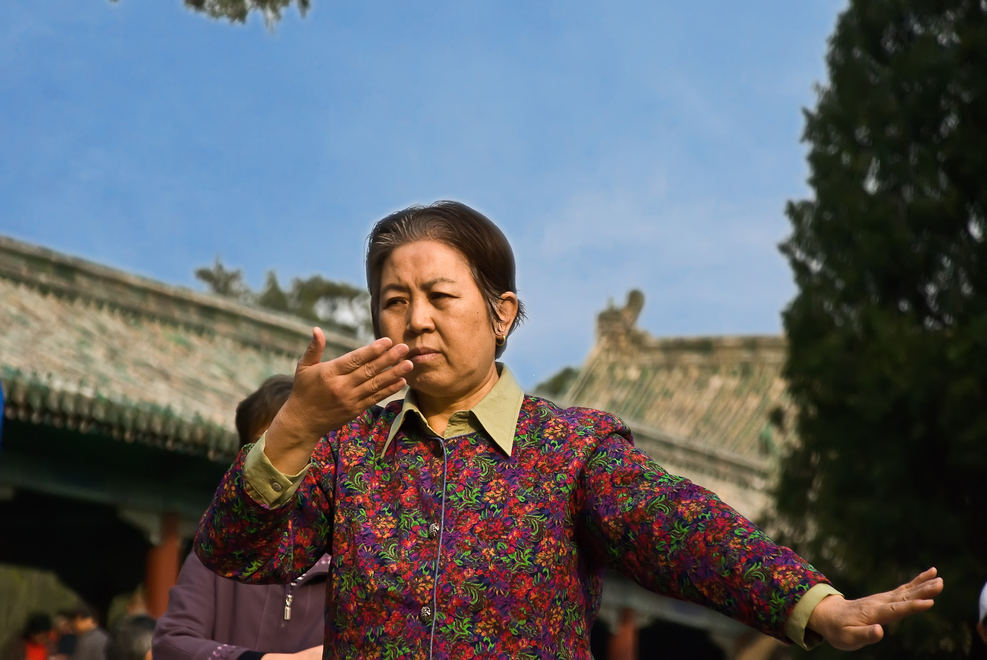 Woman in floral shirt doing Tai Chi