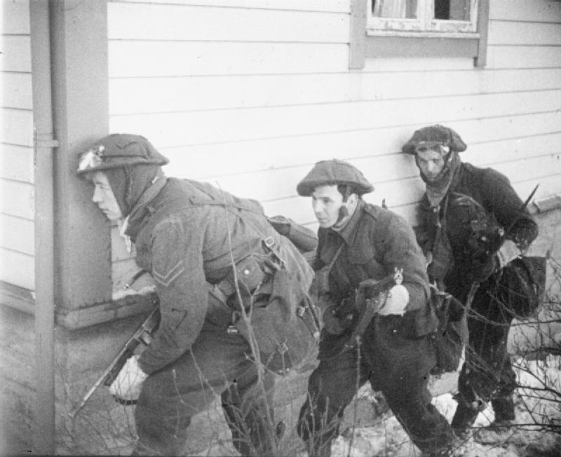three British soldiers take cover at the corner of a house