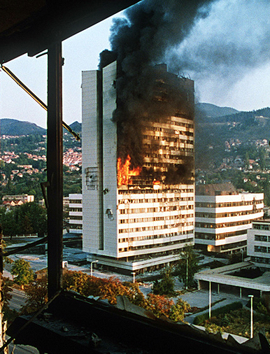 The Parliament of Bosnia and Herzegovina burns after being struck by tank fire during the Siege of Sarajevo, 1992