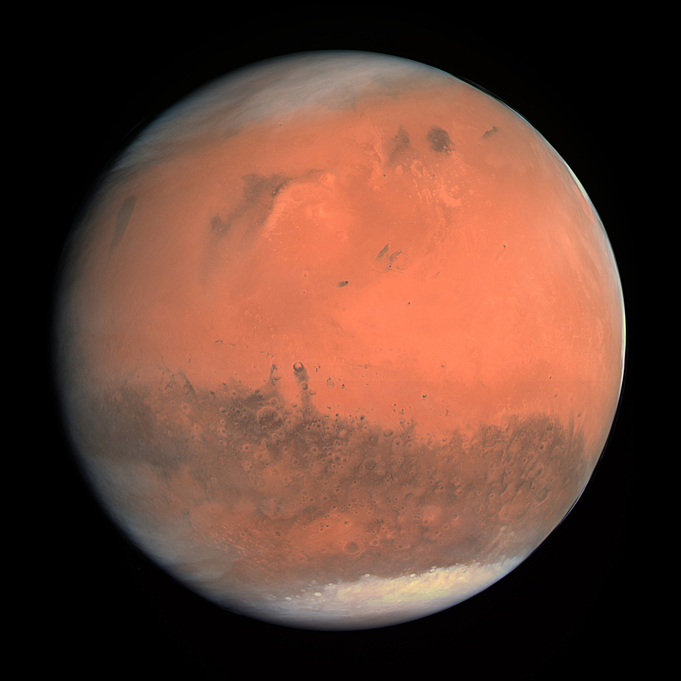 Mars Appears As A Red Orange Globe With Darker Blotches And White Icecaps Visible On