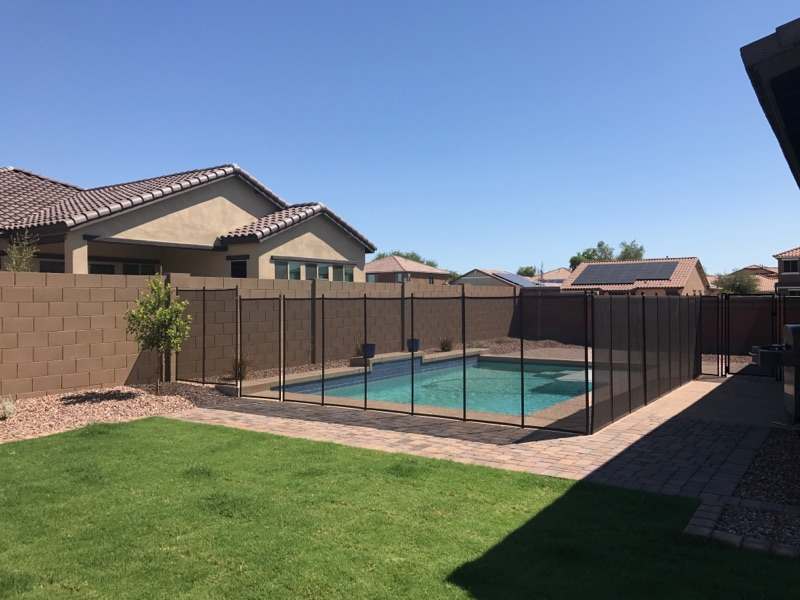 newly installed removable mesh pool fence used to provide a protective barrier between children and the swimming pool - Pool Fence Installation