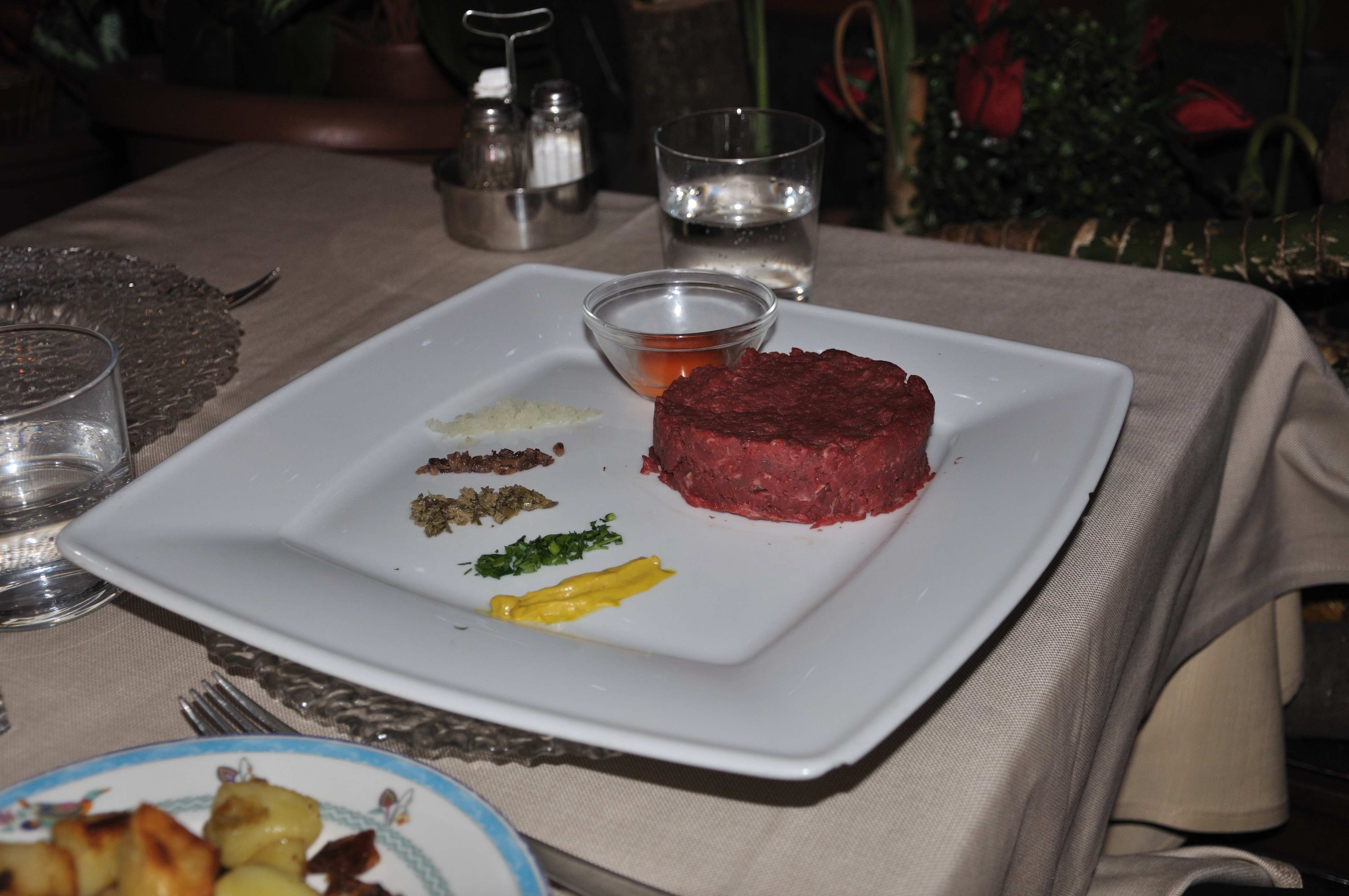 A fancy presentation of steak tartare on a square white plate with rays of chopped onion, mustard, parsley or chopped green onion, and possibly chopped bacon and a mushroom duxelle. An egg in a glass bowl is also present.