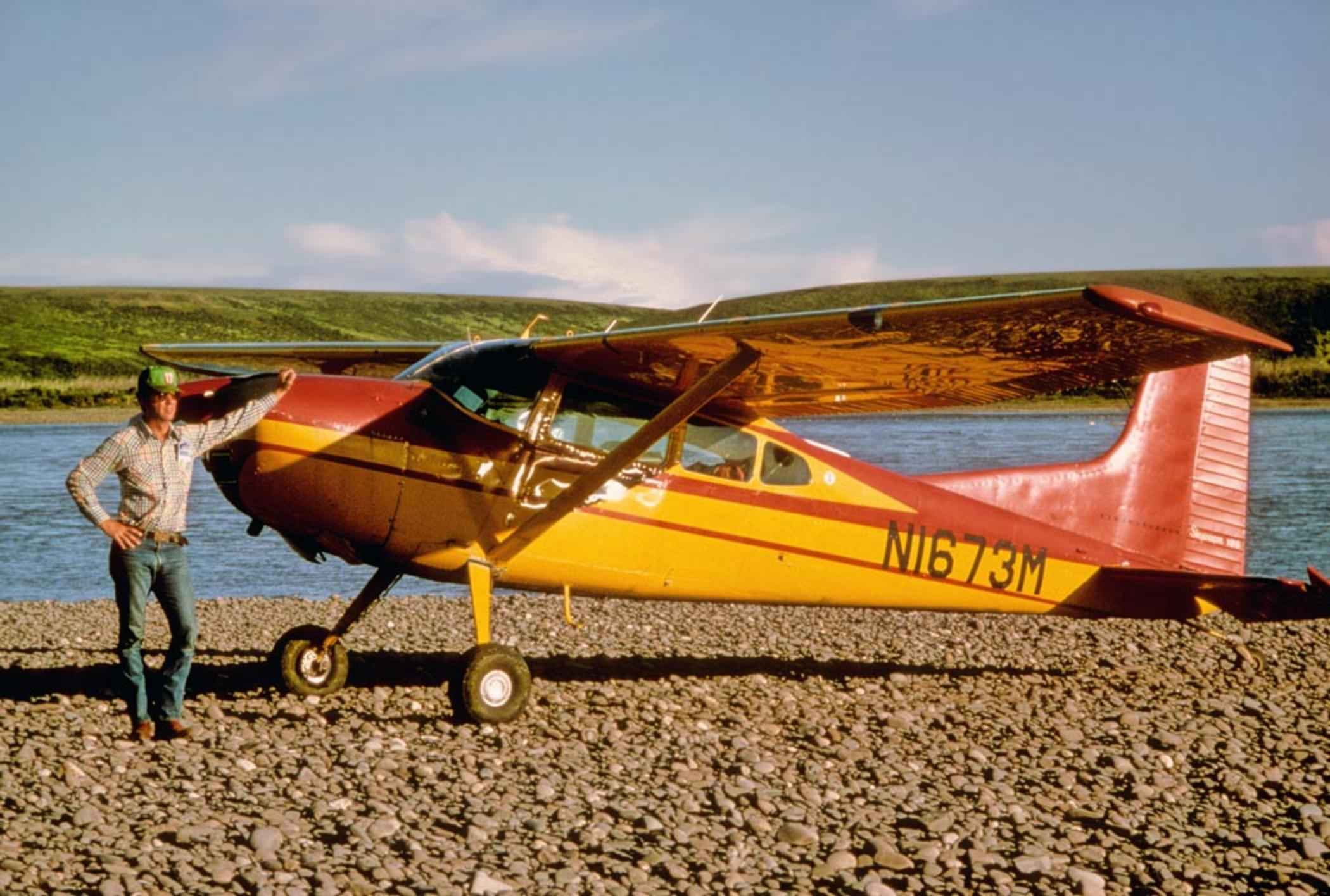 file cessna 185 man standing next to a small old airplane jpg