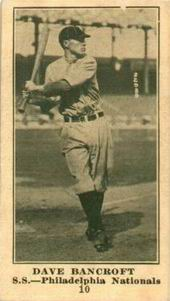 A sepia-toned baseball card of a player swinging his bat at a pitch.
