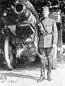 A black and white image showing Edwards in his military uniform standing next to a large cannon.