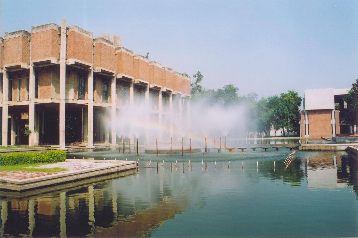Low modern building, with large pool and fountains in front