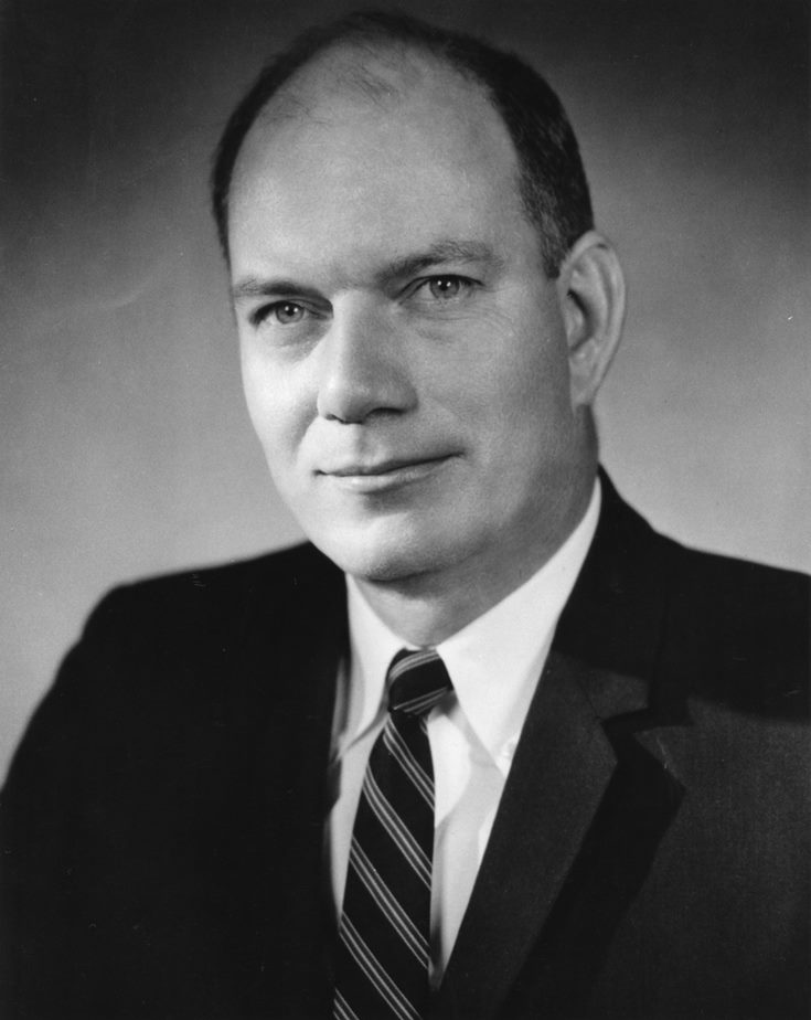 Black and white photo of a balding man in a suit and striped tie