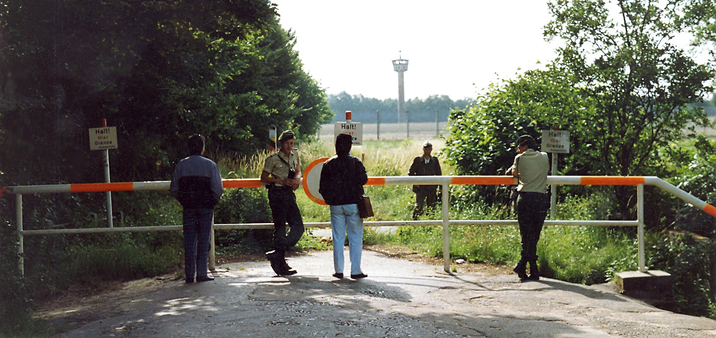 View of a road terminating in a red and white horizontal barrier, with trees on either side. Four people, two in uniform, are standing on the near side of the barrier. On the far side is another uniformed man standing in a grassy field. In the far background is a high metal fence and a tall watchtower with an octagonal cabin at its top.