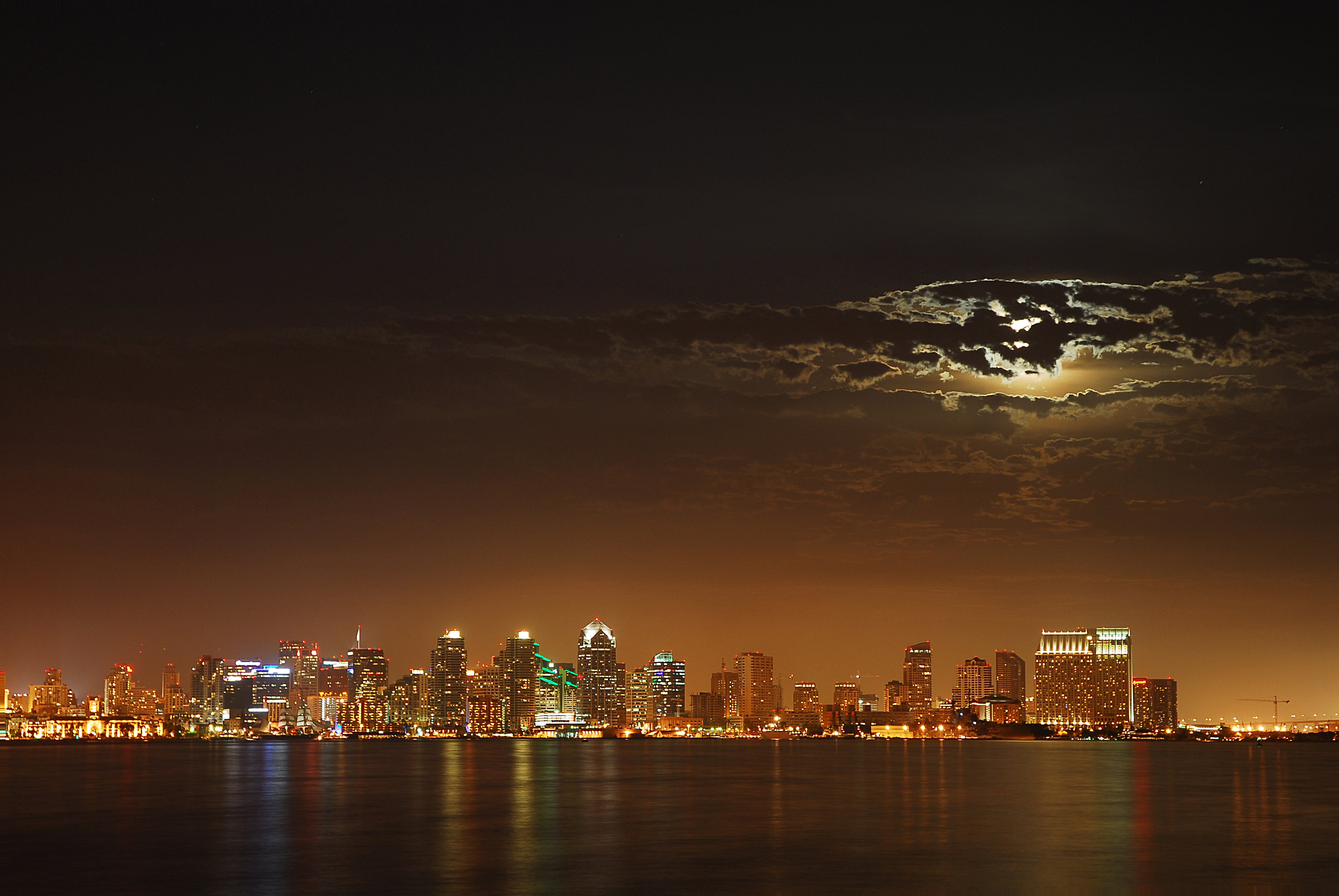 Moon peeking out of clouds over City