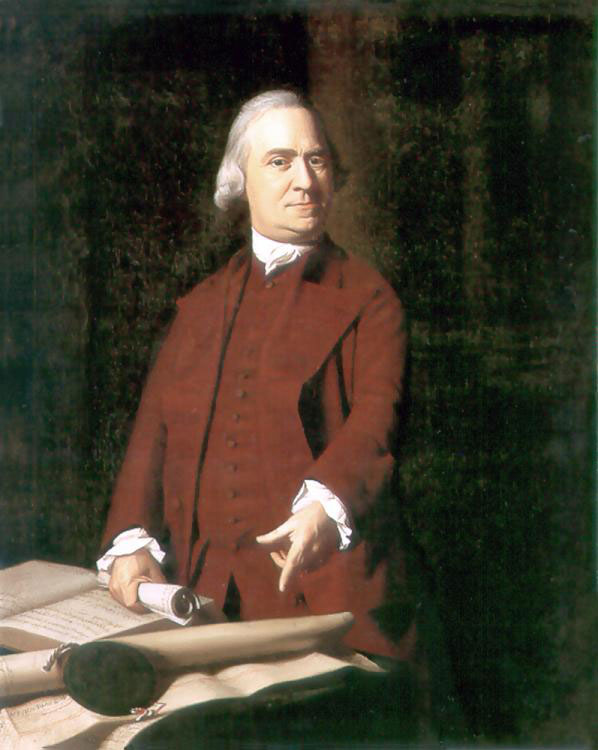 Samuel Adams standing behind a desk and pointing at a scroll.