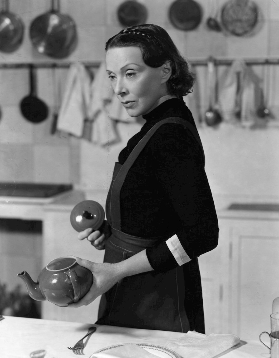 "An image of Eugenie Leontovich in ""Tovarich"". In the image, Leontovich where's the garb of a domestic worker: apron, a dark-colored long-sleeved top with cuffs rolled up about halfway on the forearm. She holds an open teapot in her left hand nearer the camera and holds the teapot's lid in her right hand with the handle towards the camera. Behind her, in soft focus, we see a kitchen counter with cooking utensils, pots, pans, and rags hanging above on the wall. I enjoy this image and find it to be aesthetically pleasing"