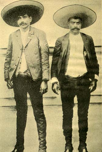 Undated photo of Emiliano Zapata (right) and his older brother Eufemio (left), dressed in the charro fashion of the countryside. Some posthumous artistic renderings of Zapata show him dressed as an ordinary peasant. Euphemio y Emiliano Zapata.jpg