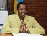 Jeannette Kagame shown sitting at a desk at a public event, wearing a green jacket