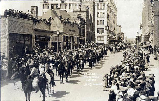 Hundreds Of Men On Horseback March Down A City Street As