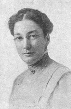 White woman wearing glasses and a high-necked blouse; her dark hair is parted at center and braided across the crown.