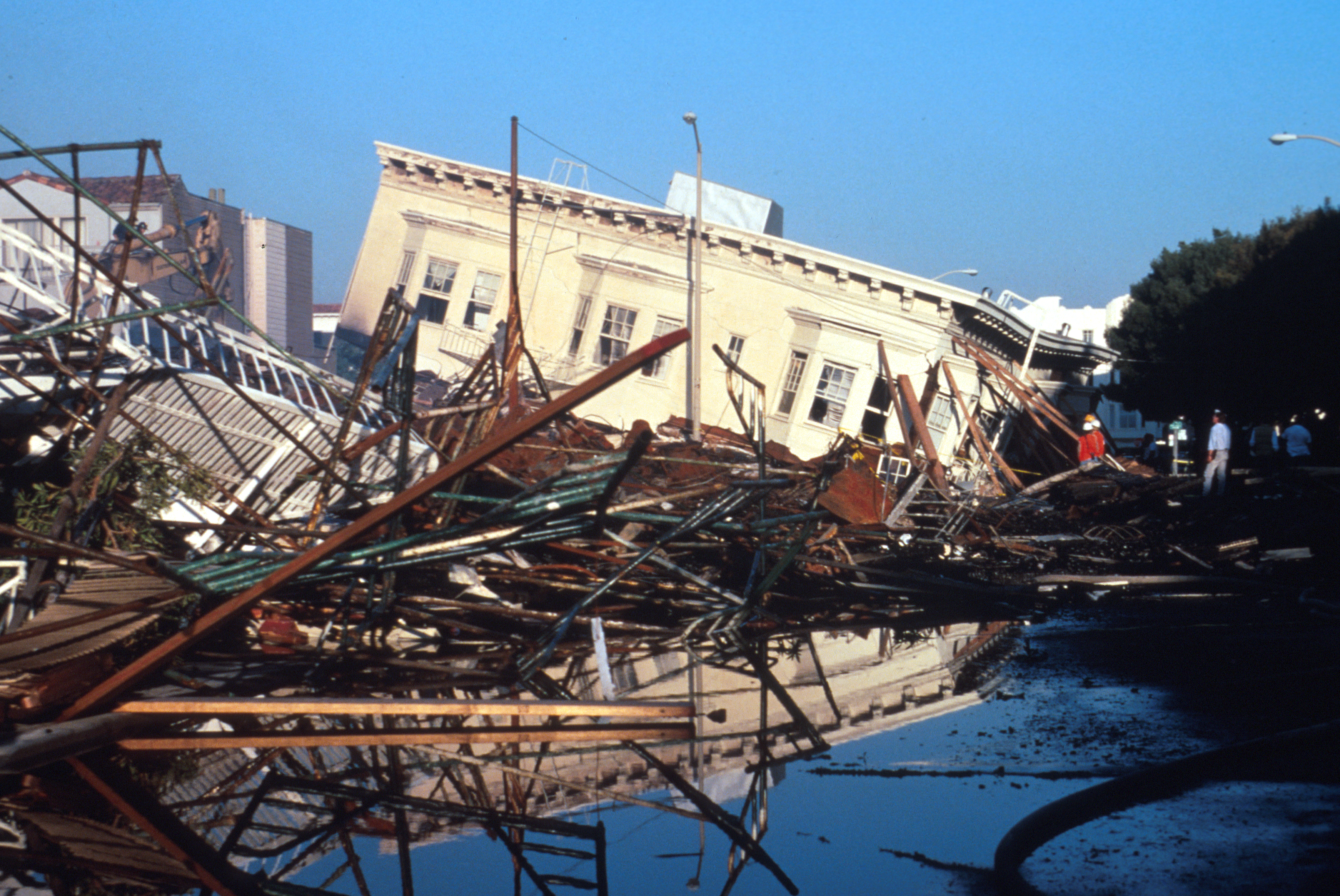 View of collapsed and burned buildings at Beach and Divisadero in the Marina District in San Francisco after the Loma Prieta earthquake, October 17, 1989. Photograph courtesy of Wikimedia commons via U.S. Department of the Interior U.S. Geological Survey.