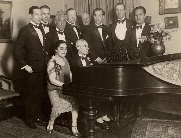 En una celebración por su cumpleaños el 7 de marzo de 1928, Ravel fumando y sentado al piano con la cantante Éva Gauthier, a la derecha (de pie y con un pañuelo en el saco) el director Leide-Tedesco, y al extremo derecho, de pie, George Gershwin. Foto de la gira americana del compositor.