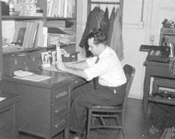 Engineer using a slide rule. Note mechanical calculator in background.