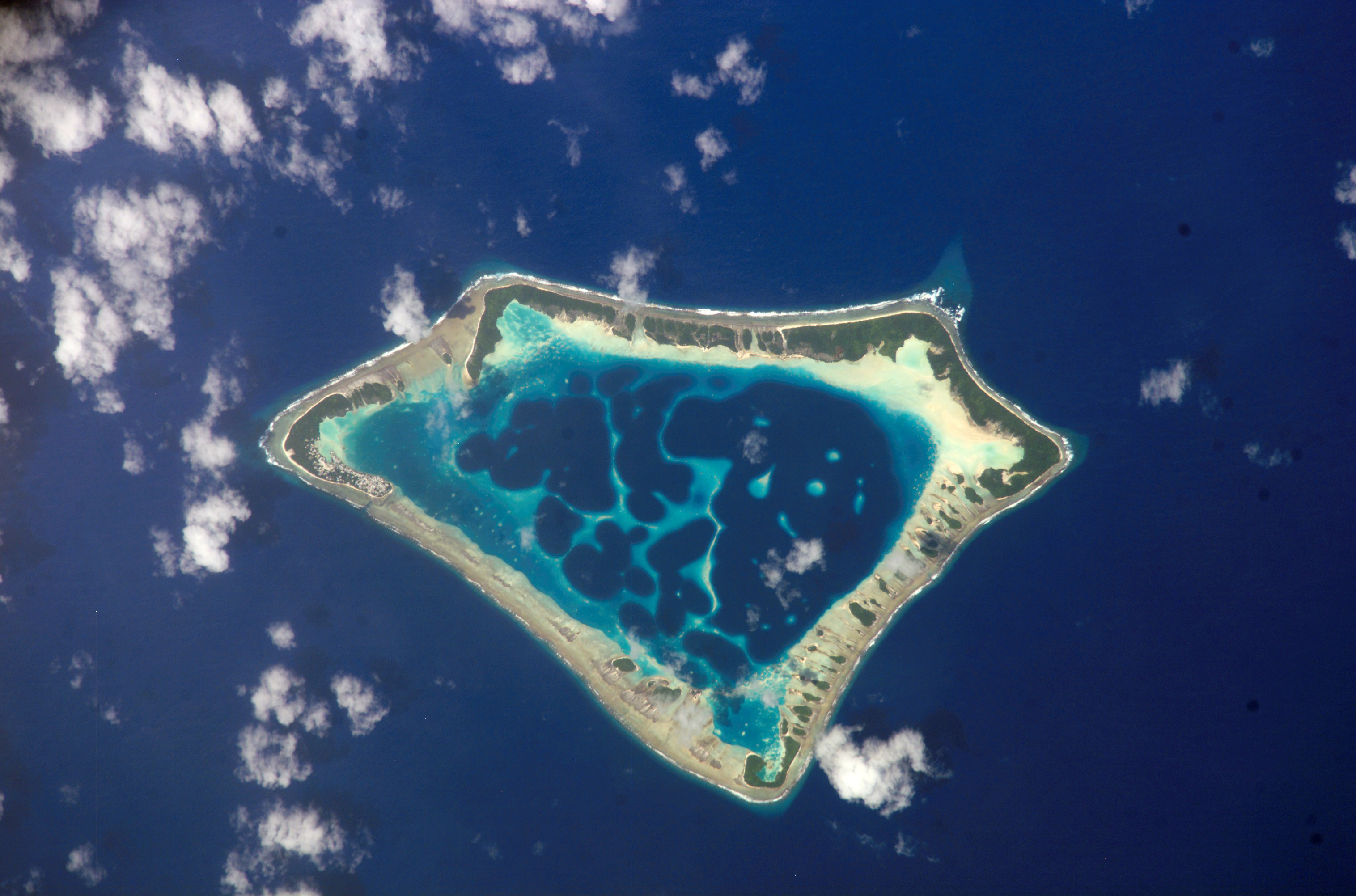 A ring-shaped island with a shallow lagoon in the interior and deep blue ocean water surrounding. Where visible, the island ring itself is white with greenery.