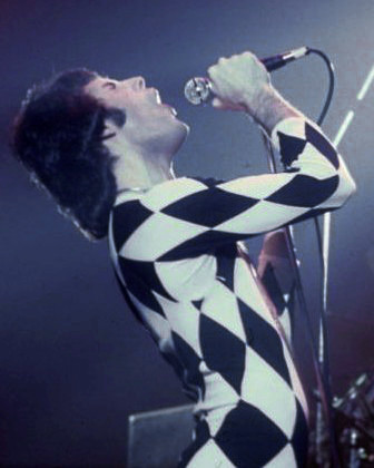 "Mercury performing in a Harlequin outfit. He appeared in a half black, half white version in the music video for ""We Are the Champions"". FreddieMercurySinging1977.jpg"