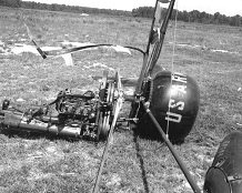 The shattered remains of a small helicopter-like craft lay on their side on the ground following an accident.