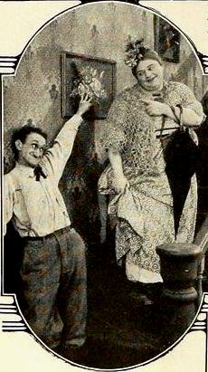 Still from the American film Love (1919 film) with Frank Hayes and Roscoe Arbuckle, on page 20 of the June 1919 Film Fun. The still caption states: that Fatty returns in the make-up of a hired girl. Father proves flirtatious.